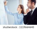 two focused coworkers looking... | Shutterstock . vector #1119664640