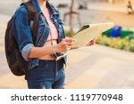 Small photo of Hipster young girl backpack tourist hand holding a map for search and plan her tour.Woman traveler touring in the summer.
