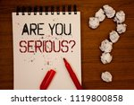 Small photo of Conceptual hand writing showing Are You Serious Question. Business photo showcasing Have to be kidding me Disbelief Is it for real Ideas on notebook wooden background quotation mark.