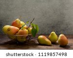 Small photo of fresh pears with leaves in a basket on wooden table