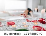 Stock photo woman lying in bath rose petals burning candles 1119885740