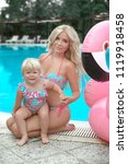 Small photo of Summer family vacation. Fashion look blond girls portrait. Beautiful Mother holding her little daughter, wears in swim wear posing with Inflatable Flamingo Pool Float by swimming pool on resort.