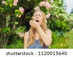 young woman sneezes in the park ... | Shutterstock . vector #1120015640