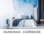 grey and blue bedding on bed in ... | Shutterstock . vector #1120066106