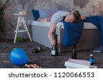 Small photo of Anniversary party. Sozzled mature man touching bottle and napping on bed