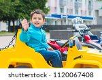 brunette boy rides an electric...   Shutterstock . vector #1120067408