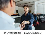 car mechanic passing car keys... | Shutterstock . vector #1120083080