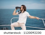 Small photo of Caucasian Bearded Traveller Man looking through binoculars from the boat, adoring beauty and power of the Ocean