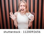 Unhappy Young Woman Is Holding...