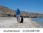 man with his dog on the beach. | Shutterstock . vector #1120108730