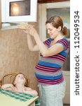 pregnant woman warms up food in the microwave - stock photo