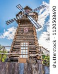 Small photo of Landscape- magnificent wooden windmill during the day with a sky blue sky