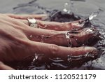young woman hand splashing in... | Shutterstock . vector #1120521179