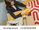 young woman unpacking unboxing... | Shutterstock . vector #1120560398