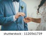bridegroom put an engagement... | Shutterstock . vector #1120561739