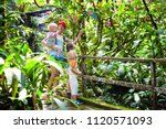 family hiking in jungle. mother ... | Shutterstock . vector #1120571093