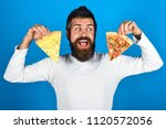 bearded man holds two pieces of ... | Shutterstock . vector #1120572056