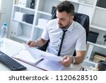 a man is sitting in the office... | Shutterstock . vector #1120628510