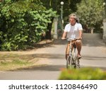 senior couple cyling in park... | Shutterstock . vector #1120846490