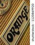 Small photo of Johannesburg , Gauteng / South Africa - June 23 2017: orange brand close up,front view of guitar amp emblem, textured material surrounding it, Daytime, vertical shot