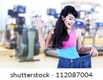 Happy asian woman posing in gym with her old big pants - stock photo