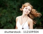 Redhead girl in the park. - stock photo