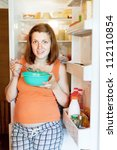 pregnant woman eating  from dish near  refrigerator at home - stock photo