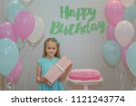 a little girl stands near a... | Shutterstock . vector #1121243774
