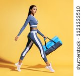 Small photo of Go to training. Sporty woman with bag on yellow background. Dynamic movement. Side view. Sport and healthy lifestyle