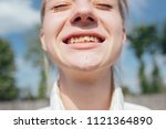 young girl smiles and shows... | Shutterstock . vector #1121364890