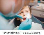 dentist examining  boy's teeth... | Shutterstock . vector #1121373596