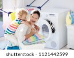 Small photo of Mother and kids in laundry room with washing machine or tumble dryer. Family chores. Modern household devices and washing detergent in white sunny home. Clean washed clothes on drying rack.
