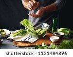 man is cooking green salad of... | Shutterstock . vector #1121484896
