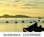 Small photo of Antonina, Brazil - Typical view of fishermen, anchored boats and ruins of an ancient building on the bay at sunrise.