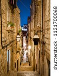 Small photo of Classic vertical view of small alleyway in the old town of Dubrovnik, in beautiful morning twilight before sunrise at dawn in summer, Dalmatia, Croatia