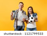 Small photo of Young win couple, woman man, football fans holding bundle of dollars money, credit card, soccer ball, cheer up support team isolated on yellow background. Sport bet, ardor family lifestyle concept