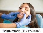 teenage girl with braces being... | Shutterstock . vector #1121931089