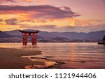 Stock photo sunset with beautiful colors miyajima torii gate in front of the shinto shrine and with mountains 1121944406
