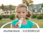 Small photo of Sweet little blond girl in green t-shirt eating her ice cream in the summer sunshine. Summer vacation, sweet dessert concept. Cute child with big eyes eat white ice cream.e