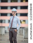 Small photo of smiling young architect or engineering builder in hard hat with tablet over group of builders at construction site, architect watching some a construction, business, building, industry, people concept