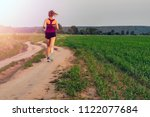 Small photo of Athletic Blonde Teenage Girl Running At Dirt road In field. Sport girl running outdoor. Young woman running in field at evening. Back view running lass on meadow at sunset. Fitness training.
