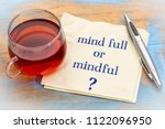 Small photo of Mind full or mindful Inspiraitonal handwriting on a napkin with a cup of tea.