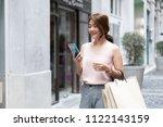 smiling asian thai girl holding ... | Shutterstock . vector #1122143159