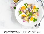 Stock photo potato salad with herring egg onion tasty snack with mustard in a white plate 1122148130