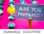 Small photo of Writing note showing Are You Prepared Question. Business photo showcasing Ready Preparedness Readiness Assessment Evaluation Words torn paper wooden clip pink background crumbled yellow blue note.