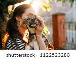 Stock photo volunteer holding homeless dog in beautiful sunset light 1122523280