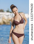 Small photo of Portrait of attractive girl on beach. Beautiful young woman in brown bikini posing arm akimbo at the sea in morning time