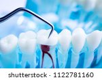 dentist cleaning teeth with... | Shutterstock . vector #1122781160