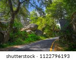 shady one lane road through... | Shutterstock . vector #1122796193