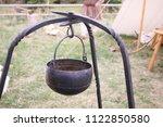 A Cast Iron Pot Hangs From A...